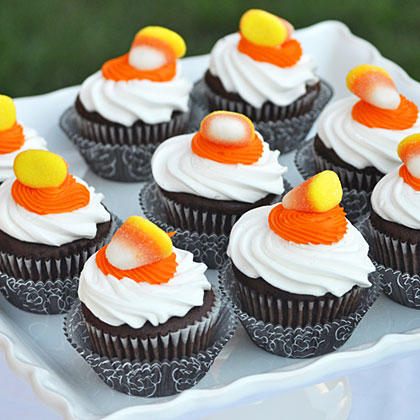 "Store-bought cupcakes get top-notch treatment thanks to fancy liners and candy corn gummies. If the icing on the cupcakes has already set, add a dollop of orange icing as ""glue"" for securing your candies."