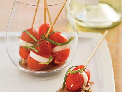 Place fresh mozzarella cheese balls, grape tomato halves and basil on short wooden skewers, and serve in stemless wine glasses for an easy and colorful presentation.Recipe:Mini Caprese Bites
